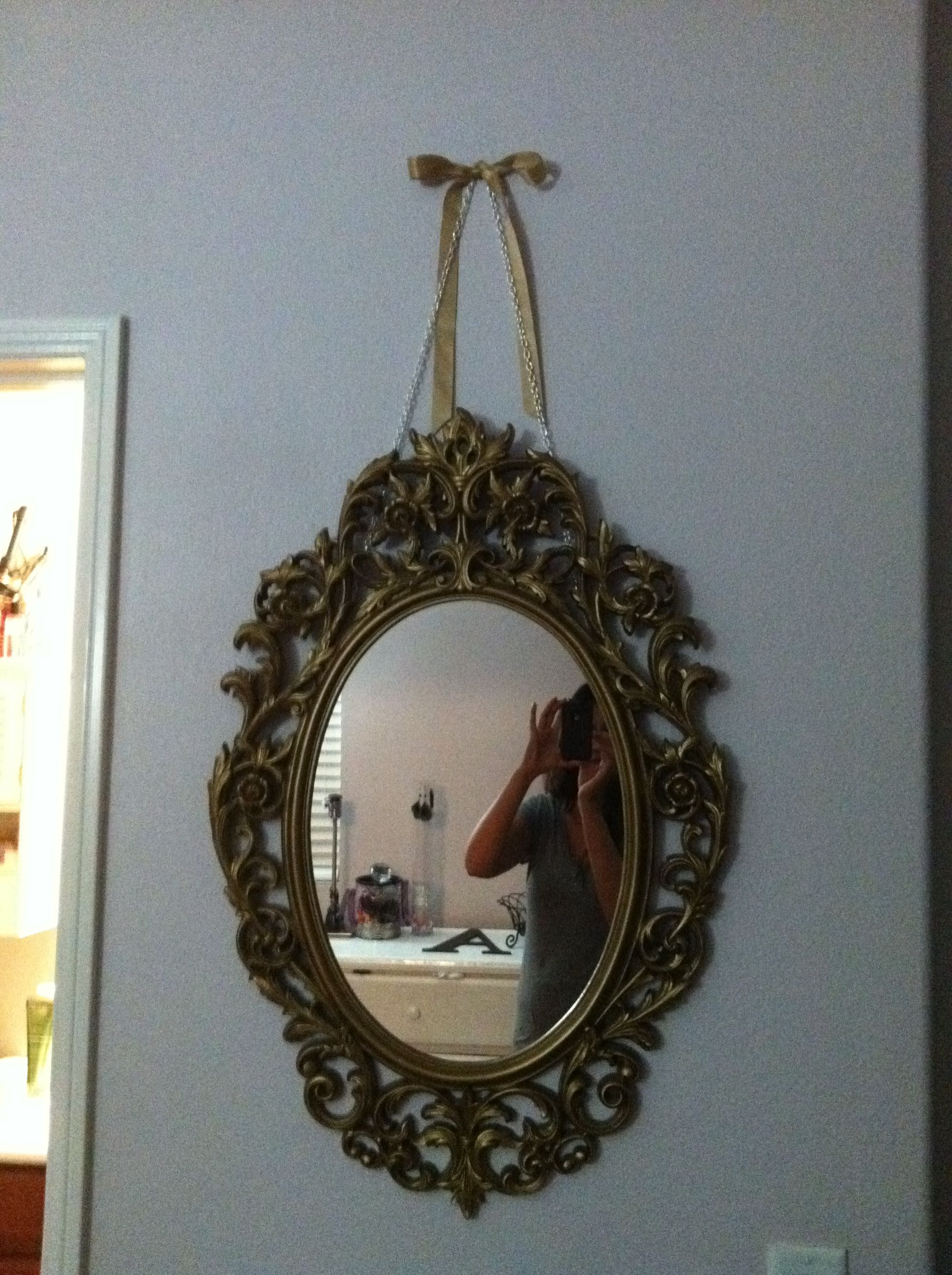 Scored this mirror at the Goodwill. I was not thrilled about the gold, but when I hung it up in my daughters room it was perfect. Hung with necklace chain and added a gold ribbon bow. <3