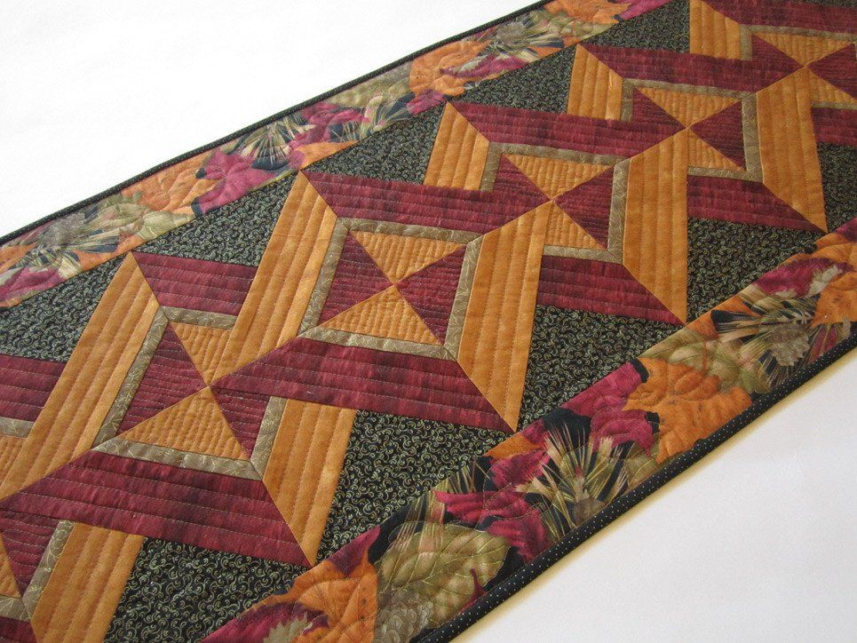 """A blend of gorgeous fall colors are stunning in this table runner There is gold metallic in a couple of the fabrics. This runner will be a beautiful setting for your table. This table runner is 19"""" x"""