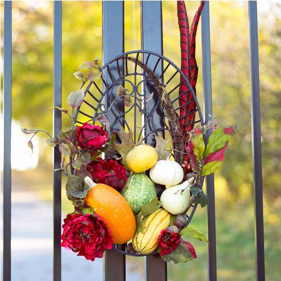 an arrangement of gourds,silk flowers, acorns, & bright feathers will last all autumn. wrought-iron basket & use crafts wire & heavy-duty glue dots to assemble