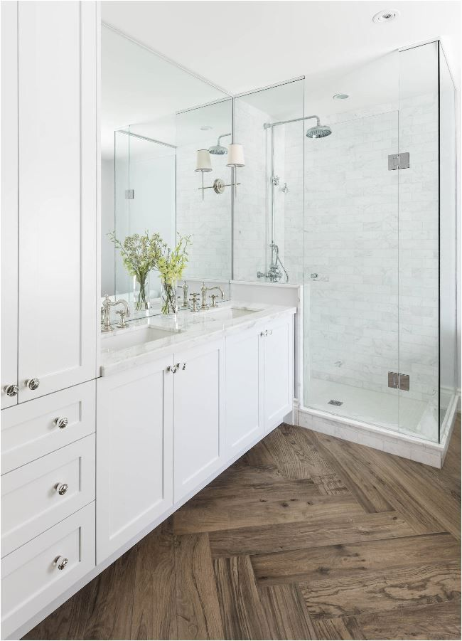 Master Bathroom With Herringbone Wood Floor Marble Shower And Countertops White Cabinets Double Vanity