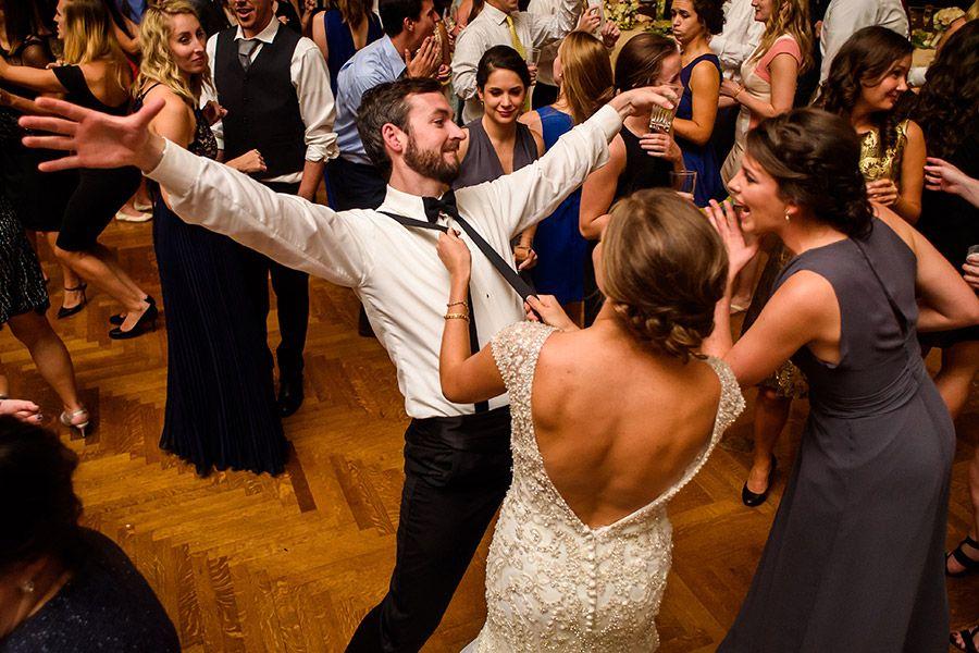 Bride Dancing And Pulling On Groomsmens Suspenders During Wedding