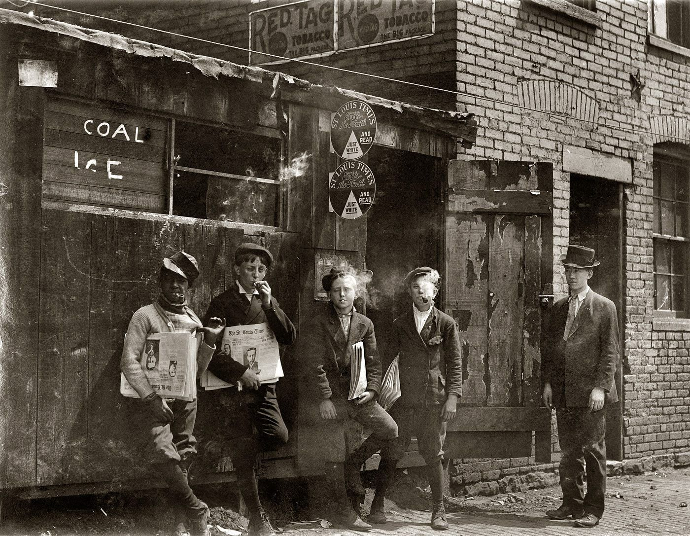 "Lewis Wickes Hine. St. Louis, Missouri. ""11 a.m. Monday May 9, 1910. Newsies at Skeeter's Branch, Jefferson near Franklin. They were all smoking."""