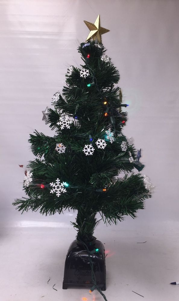 Small Pre Lit Christmas Tree With Snowflake Star Ornaments And A Larger Gold Topper
