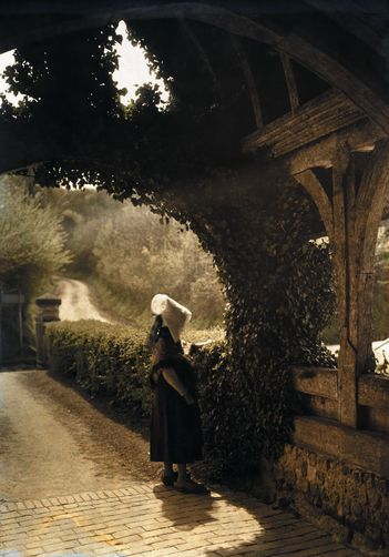 Rocques, Basse-Normandie Region, France. A Norman woman stands just outside of the old church at Rocques. Photographer: JULES GERVAIS COURTELLEMONT