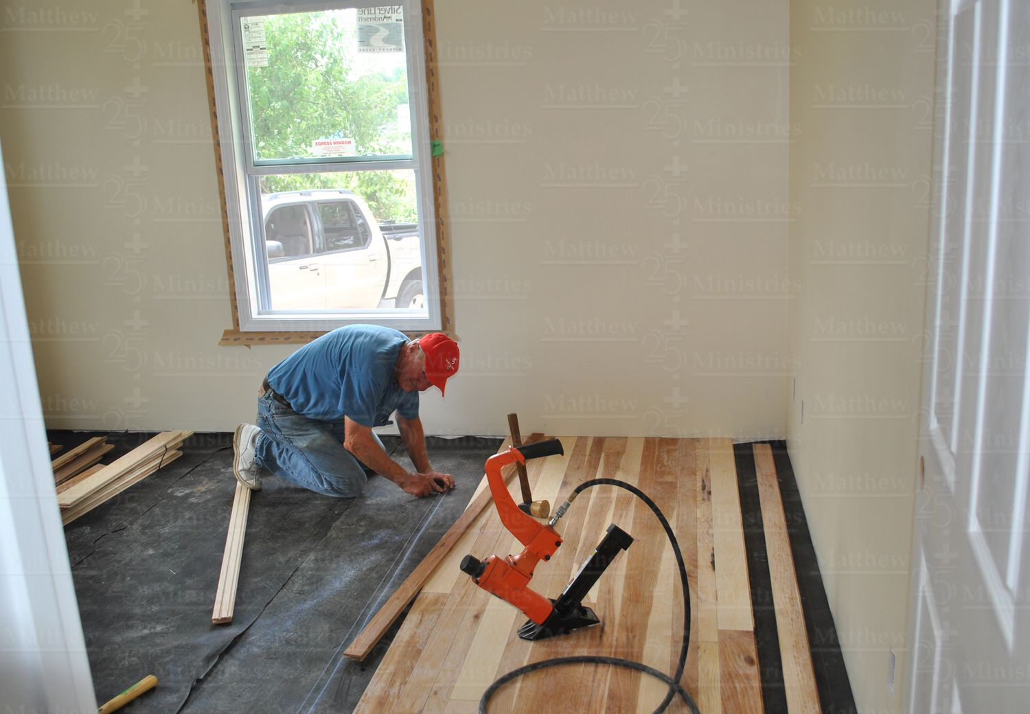 An M25M volunteer installs flooring in an Indiana home damaged by the March 2012 tornadoes