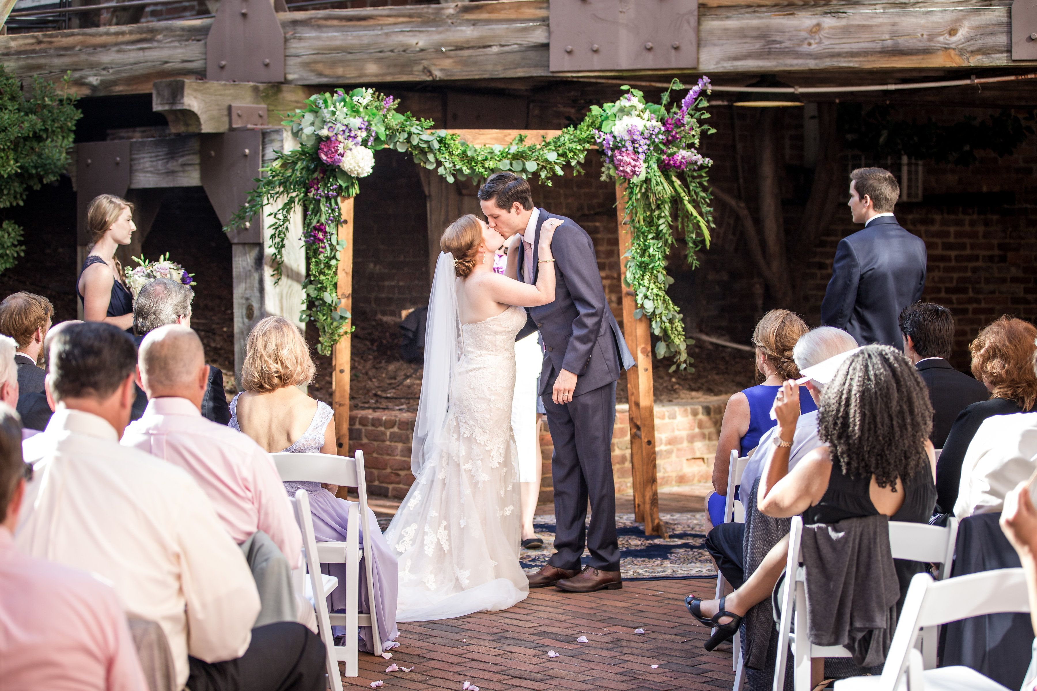 real weddings, wedding photography ideas, bride and groom, first kiss, just married, wedding ceremony, outdoor weddings, arbor, ceremony flowers, wedding flowers, The Historic Brookstown Inn, Winston Salem, purple and greenery