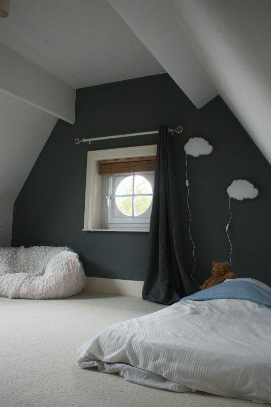 Chambre mansardée très spacieuse et lumineuse avec grand velux et fenêtre ronde moquette blanche sur parquet murs blancs et gris radiateur en fonte