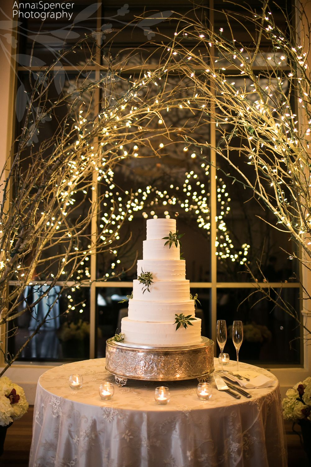 White Wedding Cake Surrounded By Branches And Twinkle Lights