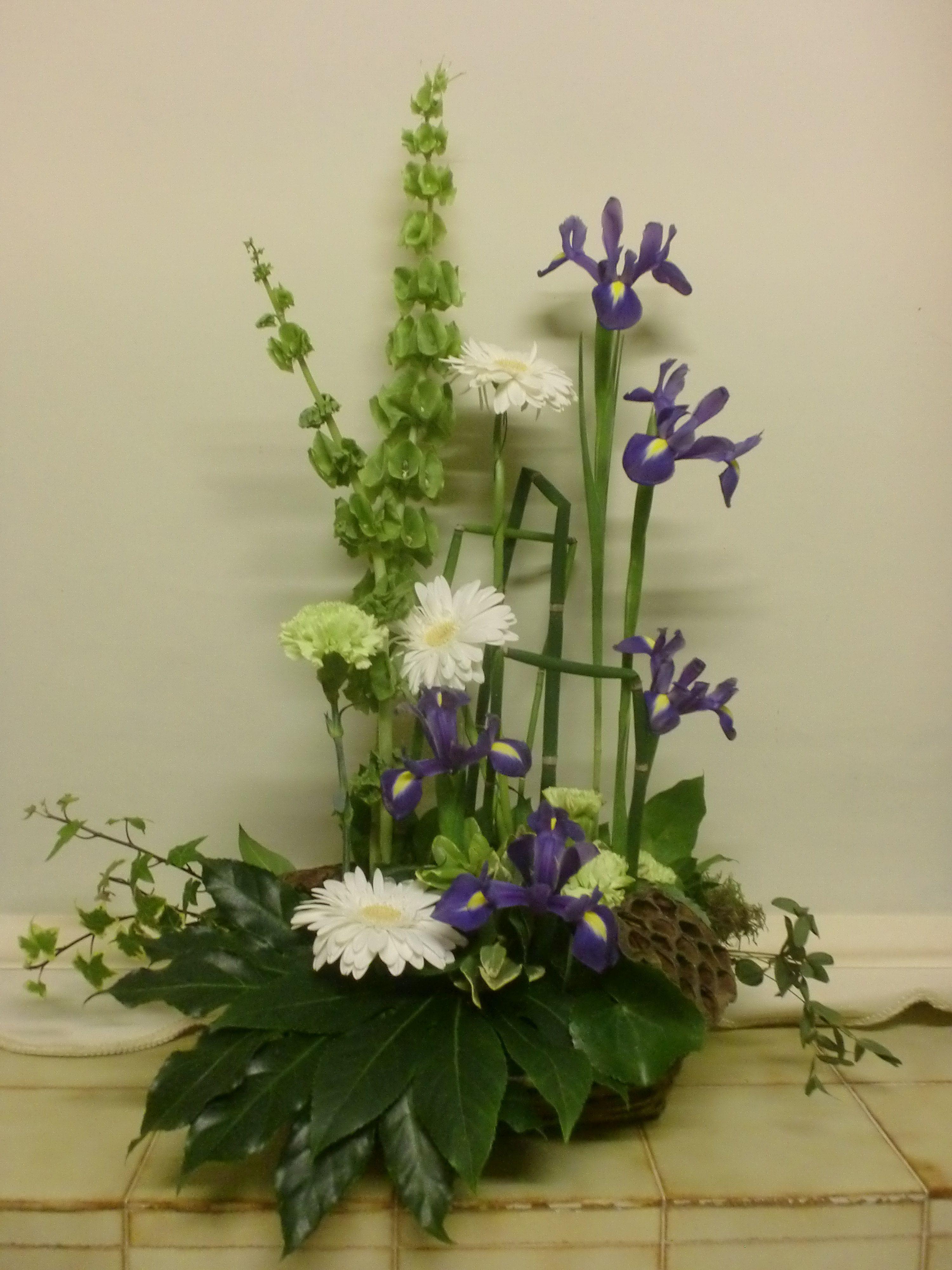 Form Linear Arrangement Using Iris, Molucella, Gerbera And Standard Carnations
