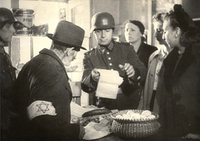 Poland, 1940, A German policeman inspecting a Jewish store. A staged photograph that was part of the German police curriculum. The Jews in the ghetto had no such nice stores stocked with food at all.
