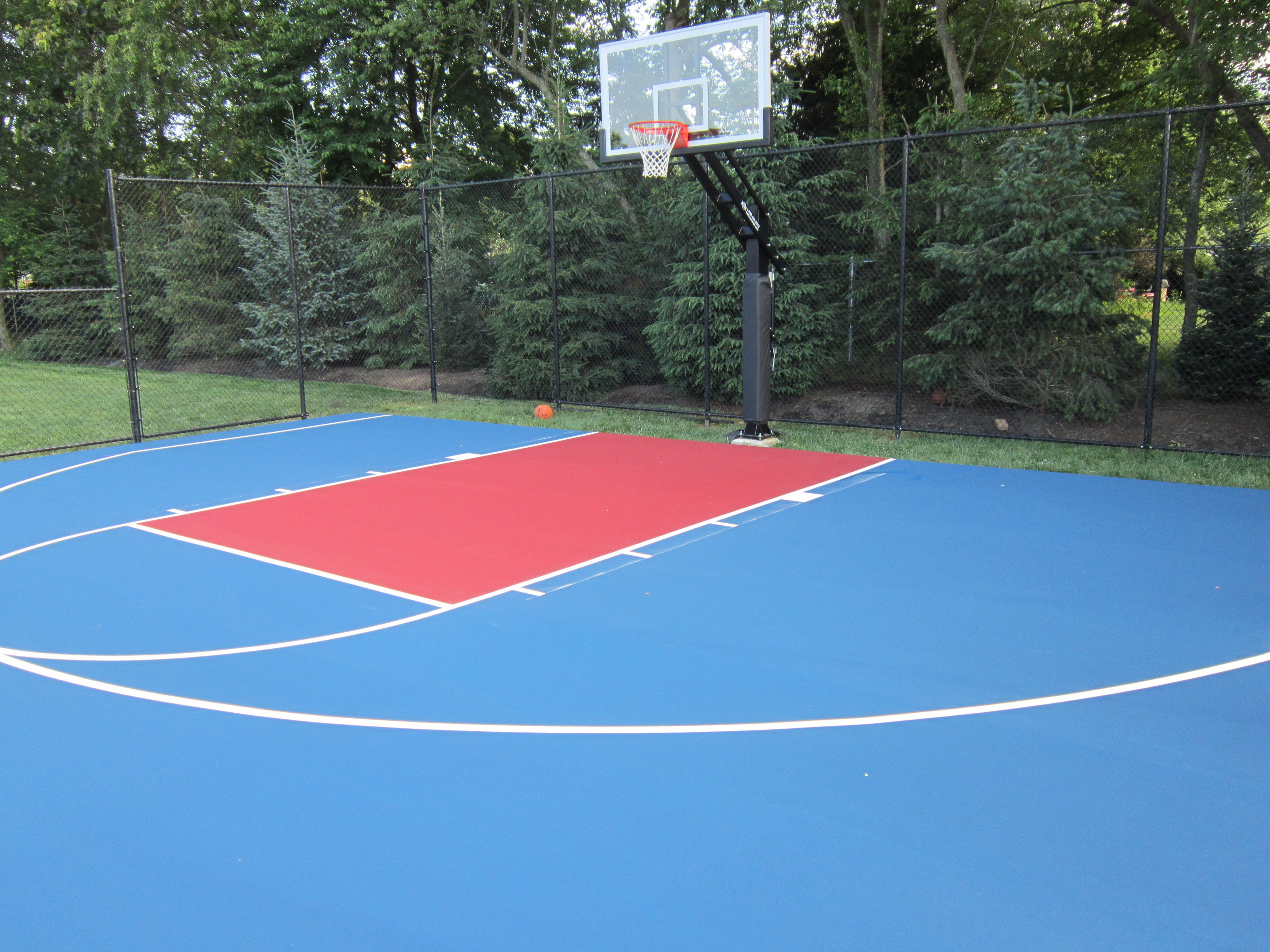 this is a royal blue and red backyard asphalt basketball court we