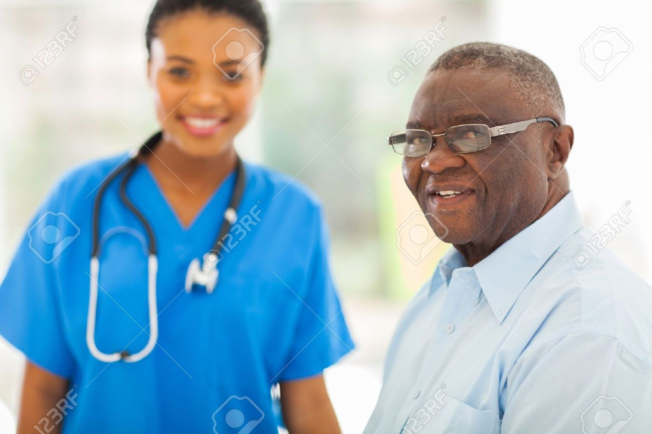smiling senior african american man in doctors office with nurse on background Stock Photo