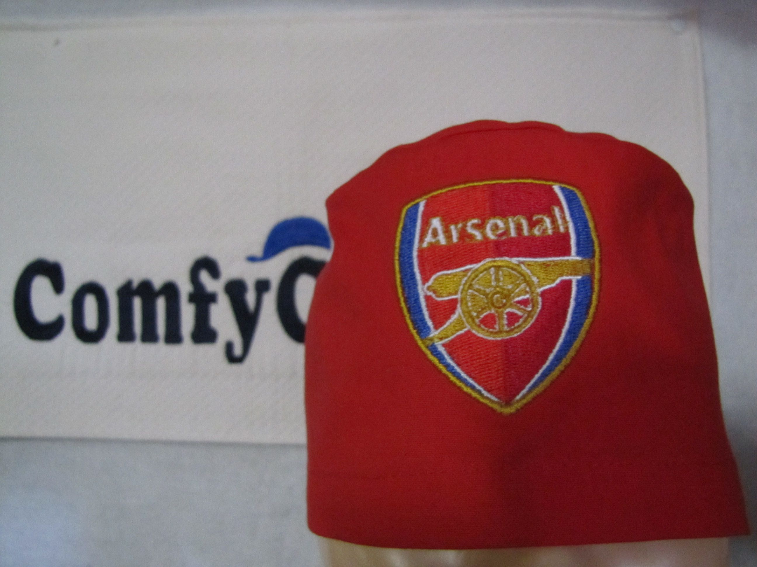 Arsenal crest embroidered on a red male scrub cap.