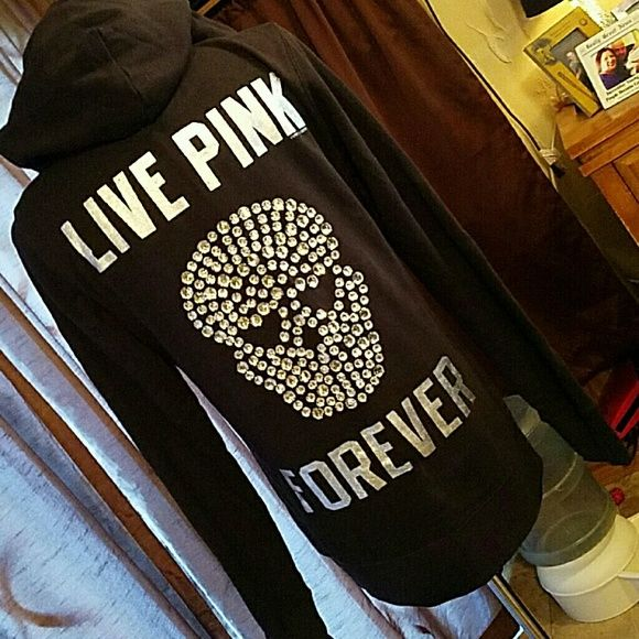 """PINK by VS Black XS Jeweled SKULL Jacket *MINT* Brand: Pink by Victoria's Secret  Item: Black Hooded Zip Up Hoodie.  Yhe front has the dog on the left chest.  The back says 'Live Pink Forever' in Silver.  Below the Live Pink and above Forever there is a skull with heart shaped eyes skull done in large (for clothing) jewels.  Color: Black.  Wording is Silver.  Size: XS (although runs larger) Armpit to armpit is 22"""".  Shoulder to hem is .  Condition: Excellent, like new condition.  Worn for a…"""