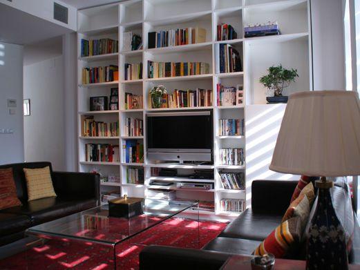 librera realizada en mdf lacado blanco integrando el televisor y una zona cerrada para almacenaje de