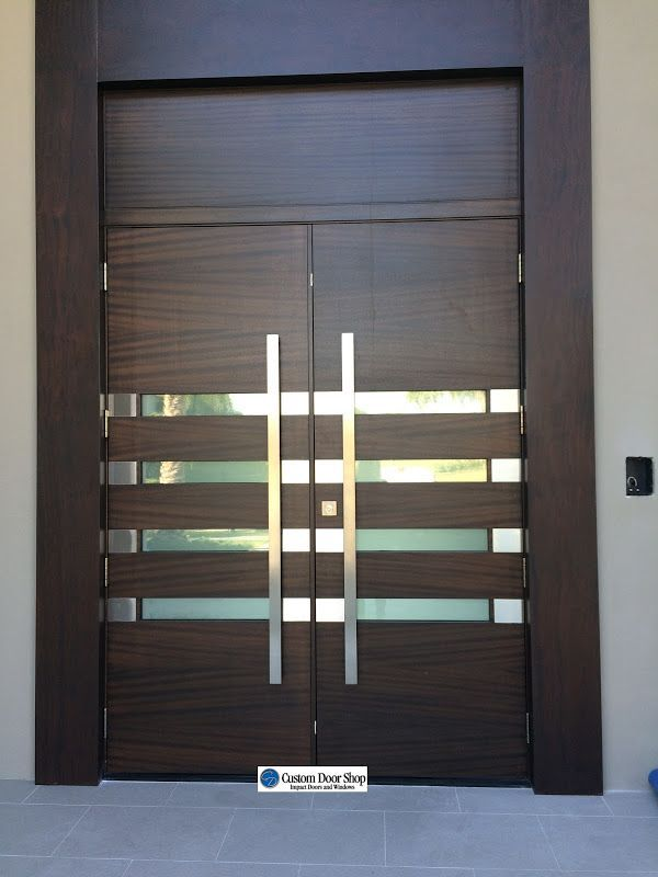 contemporary front doors.  Mahogany double wood doors with extra large stainless steel pulls and glass.  Hurricane and impact rated with style.