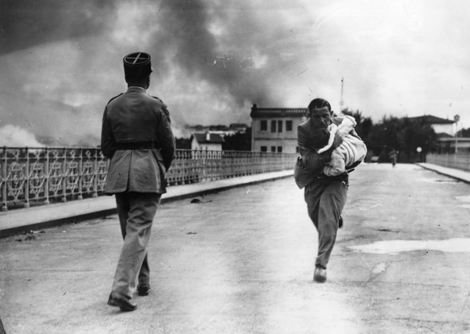 A journalist dashes across a bridge between to rescue a baby during Civil War. [1936]