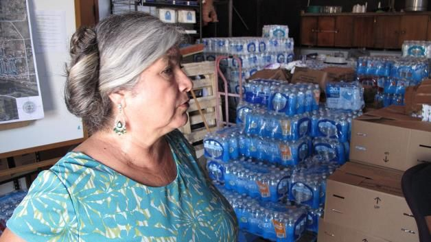 In this Monday, Sept. 15, 2014 photo, Elva Beltran, director of the Porterville Area Coordinating Council, is shown in the charity's warehouse filled with donated water in Porterville, Calif. Beltran normally works part time helping poor residents pay their power bill or fill up their car with gas so they can make it to a doctor's appointment. But now Beltran says she is working full time to help people of East Porterville whose wells have run dry amid the state's historic drought.