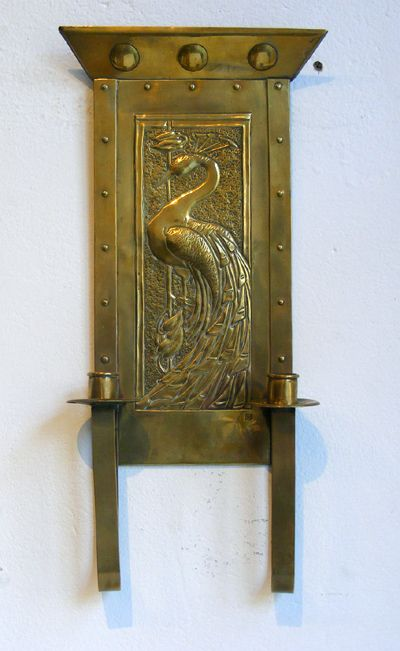 Arts and Crafts brass wall sconce with repouse work depicting a