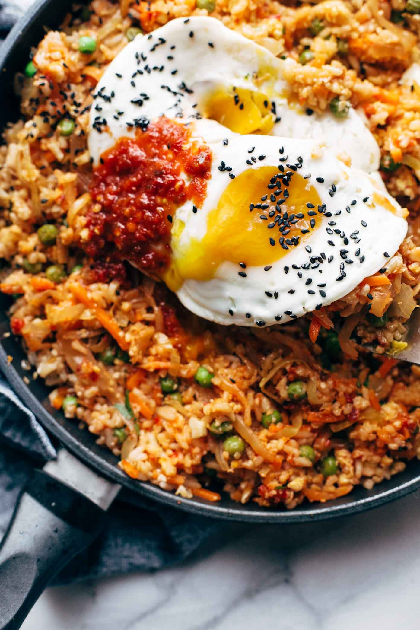 Kimchi Fried Rice FTW Cauliflower rice frozen peas and carrots fresh garlic and ginger soy sauce chili paste a forkful of kimchi and finished with a runny yolk waterfall...