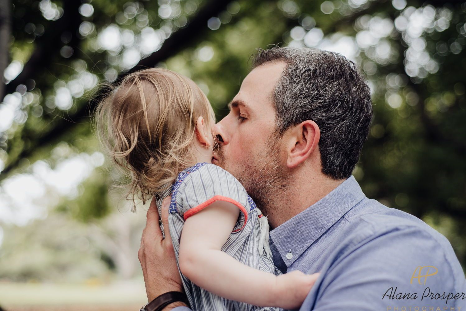 Father Holding His Toddler And Kissing Her Cheek During A Perth