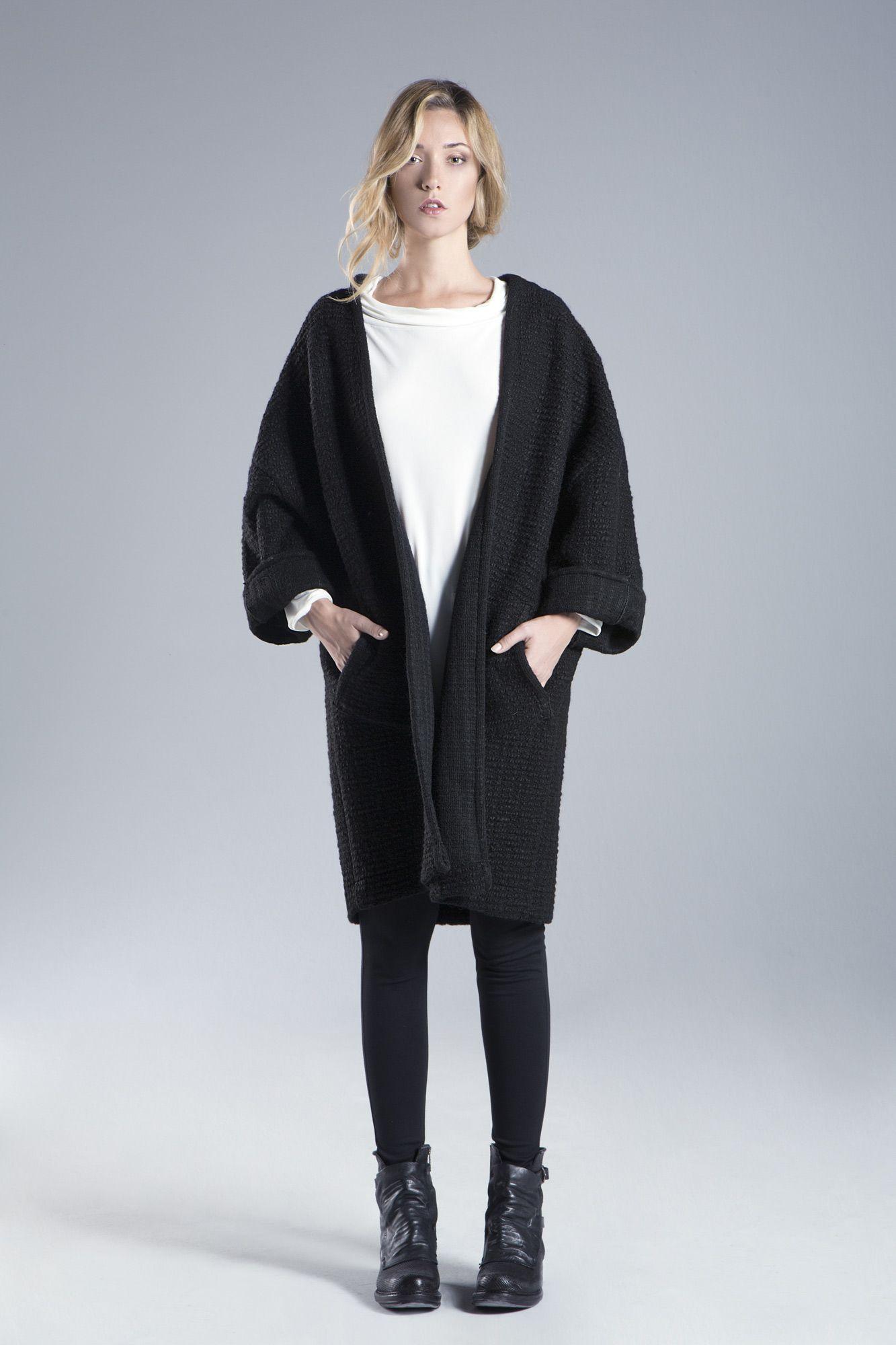 Spolverino in lana tinta unita, con le maniche da rigirare. Linea essenziale, lunghezza al ginocchio.