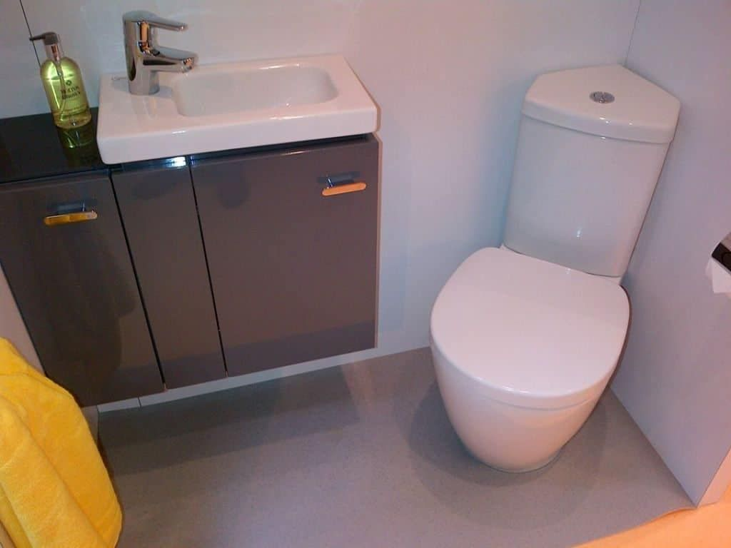 A Small Bathroom With A Corner Toilet Corner Toilet Small Bathroom Small Downstairs Toilet