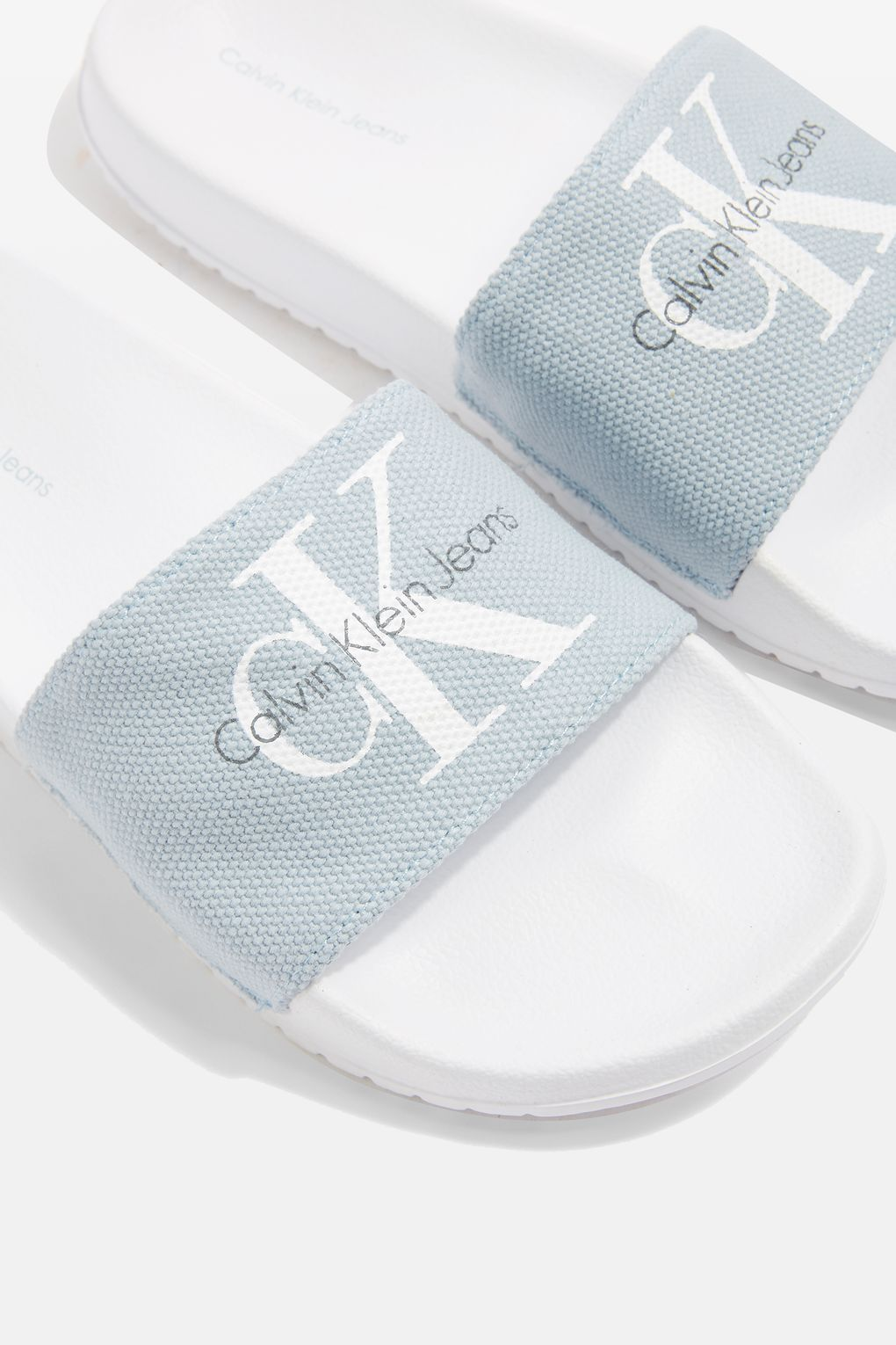 53a5da5bcbfff ... to elevate your summer footwear with the blue Jean slider by Calvin  Klein. Pair the look with frayed hem white jeans and a co-ordinating CK logo  top.