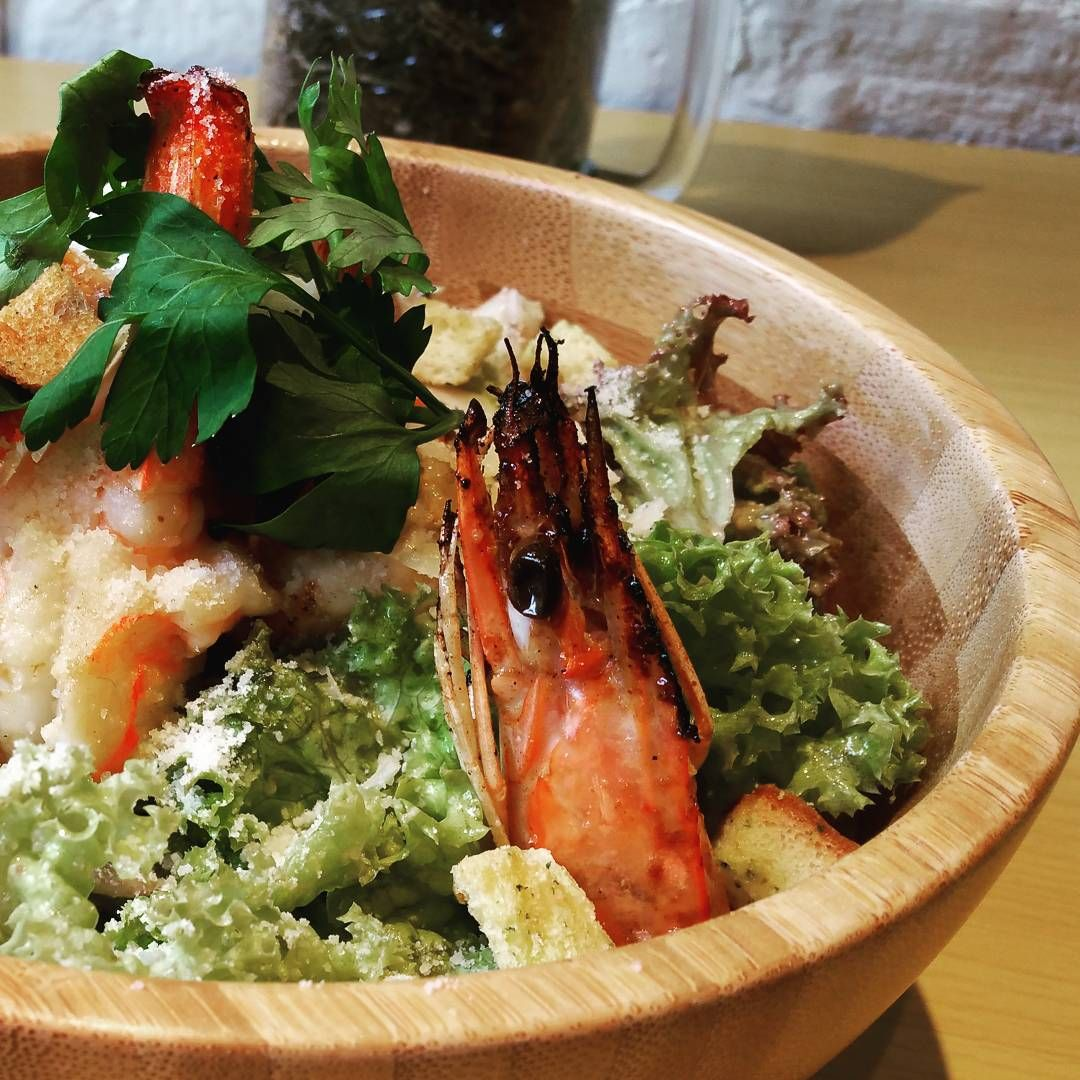 Enlivening the crunchy leaves of this Caesar salad are grilled prawns and poached eggs.
