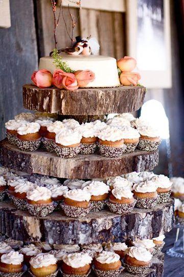 mesa de cupcakes para boda rústica sobre torre hecha con madera de