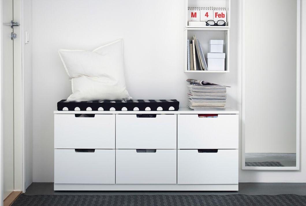 Kommode med IKEA-sitteunderlag. Helfigurspeil og åpen oppbevaring på veggen.