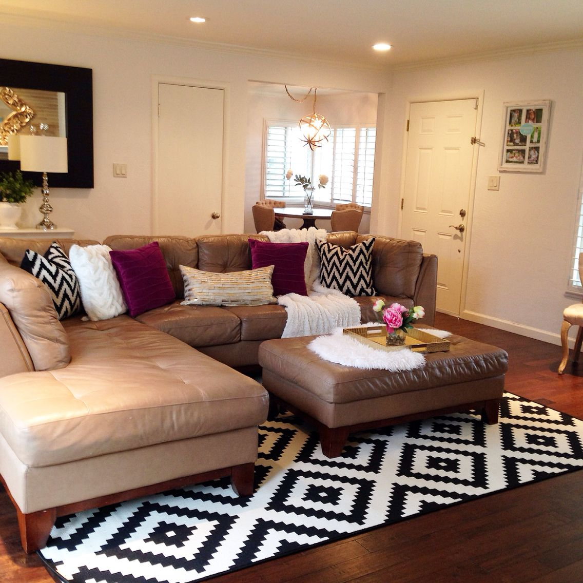black and white area rug in the living room. pops of fuschia too