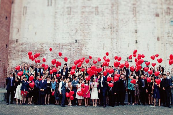 How cool do red-heart balloons make this group wedding guest shot?