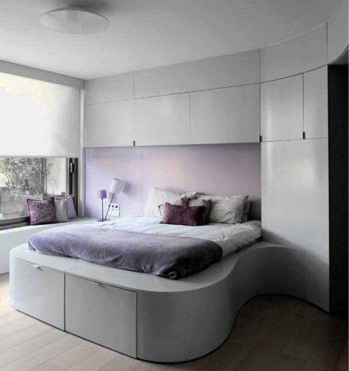 Modern bedroom with built-in, rounded-corner bed.