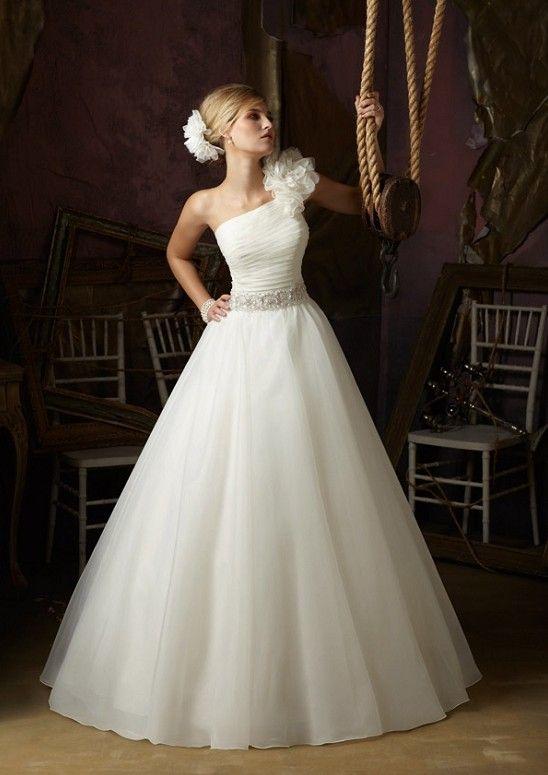 Organza over satin, princess wedding dress, with one ruffle shoulder, and crystal embellishments at natural waist.