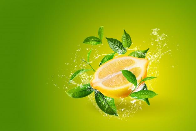 Water Splashing On Lemon And Green Tea Leaf Isolated On Green