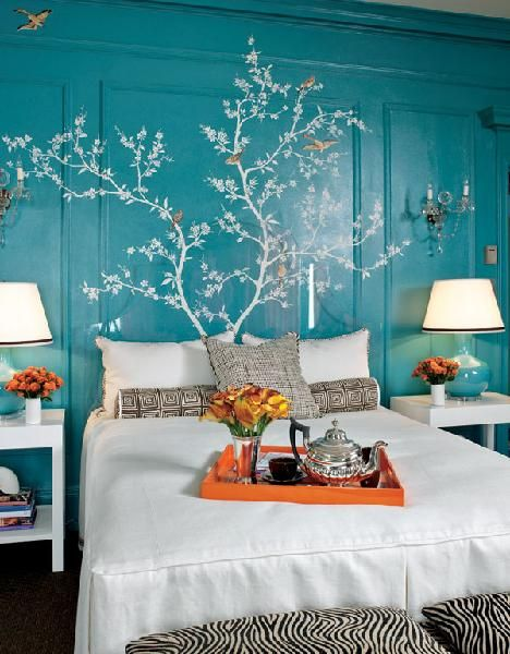 Glossy turquoise blue lacquered walls paint color, lucite headboard, white bedding, zebra benches ottomans, white nightstands, turquoise blue lamps, wall mural and orange tray.