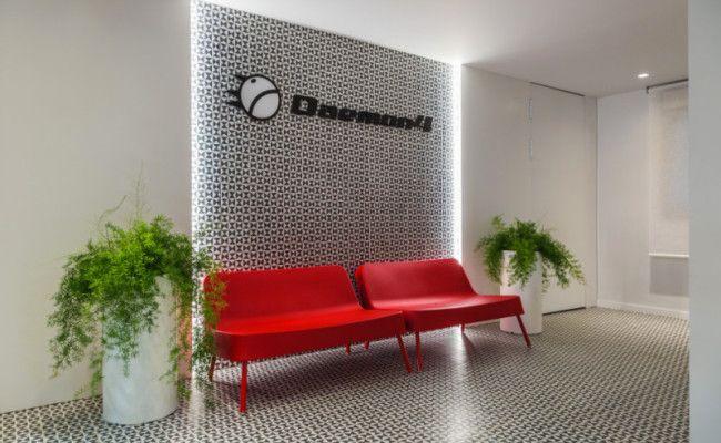 Oficinas. Zona de espera con revestimiento imitación mosaico hidráulico, diseño geométrico. Mobiliario en polietileno.