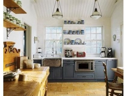 The wooden sideboard, the white boards on the ceiling, warm tan flooring, blue cabinets, vintage light fixtures and display of blue and white pottery