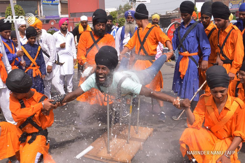 INDIA, Amritsar : An Indian Nihang, a religious Sikh warrior,  demonstrates Sikh martial arts skills known as 'Gatka' during a march  to mark the 354th birth anniversary of the Sikh warrior Shaheed Baba  Jiwan Singh at the Golden temple in Amritsar on September 3, 2015. The  Sikhs are celebrating Shaheed Baba Jiwan Singh, a famous warrior from  the Sikh religion who lived during the 17th century. AFP PHOTO/NARINDER  NANU