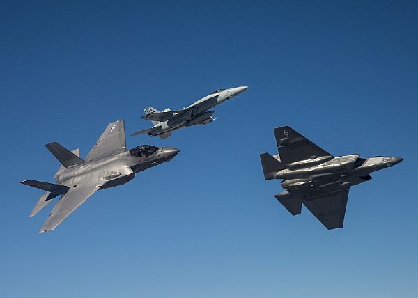 Two F-35C Lightning II aircraft before a break maneuver with an FA-18E Super Hornet from Naval Air Station (NAS) Lemoore