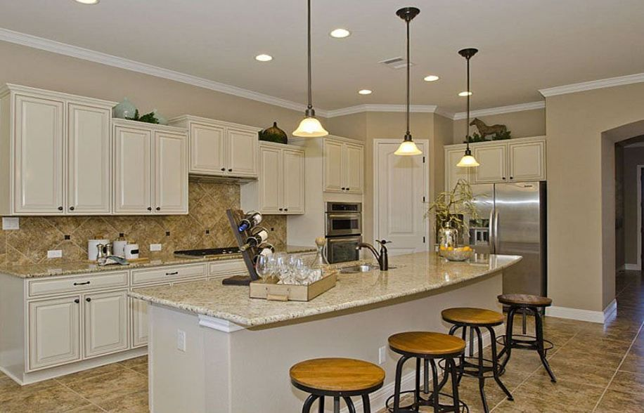 Kitchen with cream colored multi-level cabinetry with ...