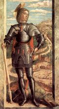 George stands, armoured and helmetless, holding a broken spear, the missing end of which is visible stuck in the mouth of the dead dragon at his feet. Behind him is a grand city on a hill