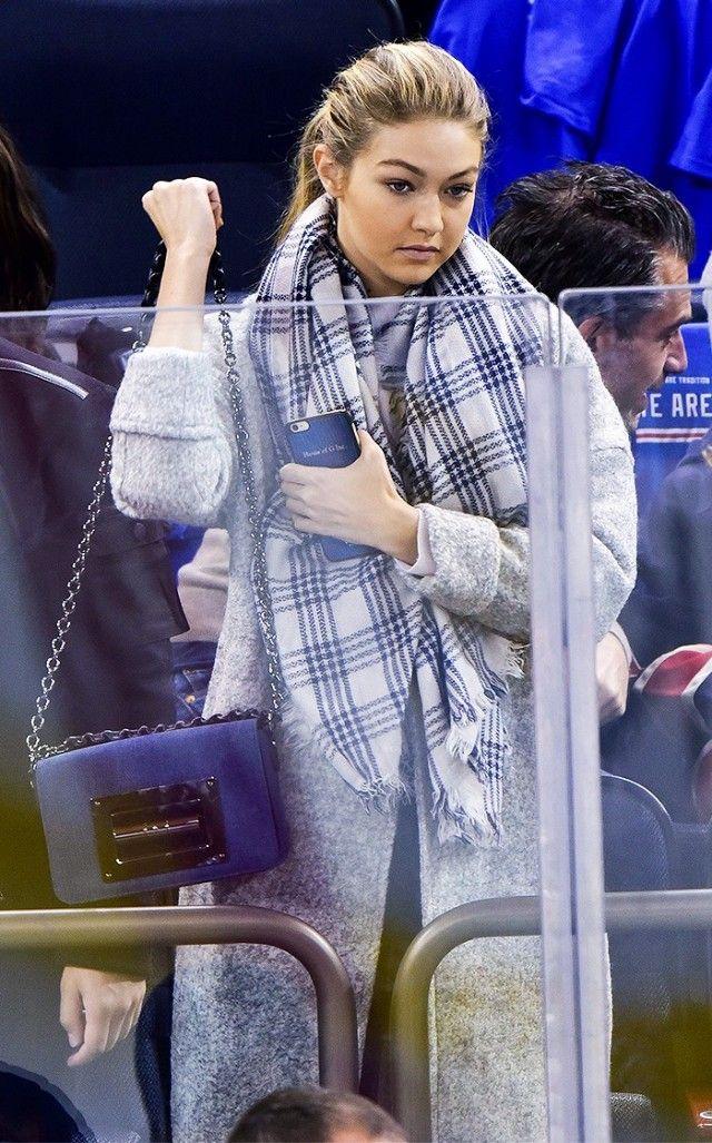Gigi Hadid wears a gray coat, plaid scarf, and Tom Ford flap bag