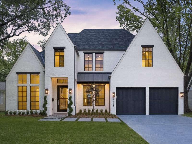 With Deep Blue Garage Doors High Pitched Roof Elongated Windows And White Exterior This Modern Farmhouse Exterior French Country Exterior Tudor Style Homes