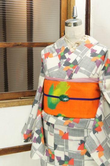 アイボリーとチャコールグレーのバイカラーで織り出された大胆な市松チェックに、ひらりと舞い遊ぶような蝶々のような、はらりと風にちりしく木の葉のようなカラフル幾何学模様が織り出されたウールの単着物です。
