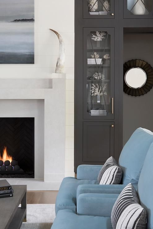 A blue art piece hangs above a light gray fireplace mantel framed by white shiplap and