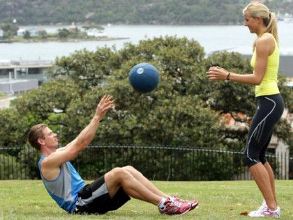 The seated partner starts to lower into a sit-up, and the standing partner passes them the ball.hold the ball above their head and keep it there for the entire down phase. Once your mid-back touches the ground, pause and rise. Once you are just short of the top of the movement, throw the ball back to your partner.
