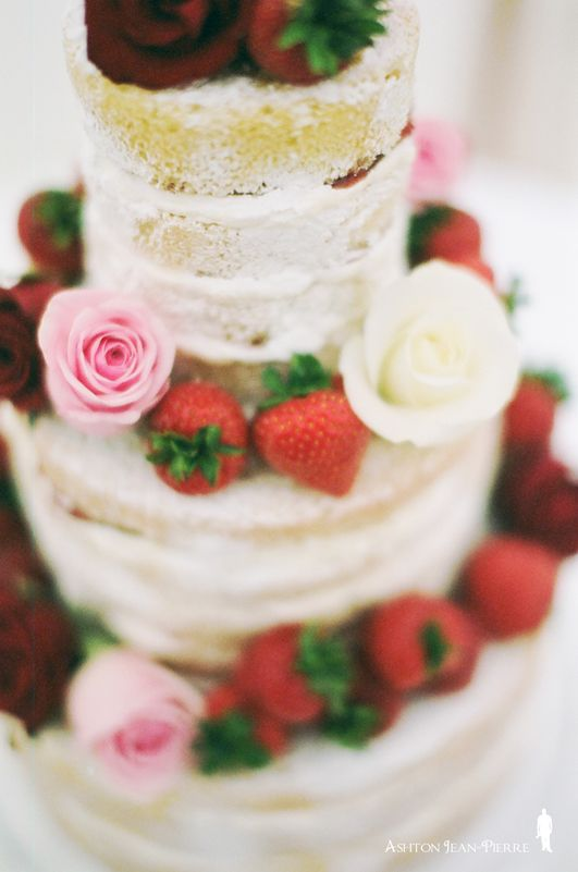 naked cake topped with strawberries and roses