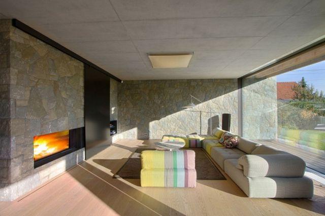 Steinwand Laminatboden Sofa Bunter Sessel Kamin Glasfronten